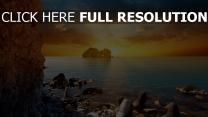mer rock lever du soleil nuageux