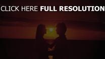 étreinte couple coucher du soleil mer romantique